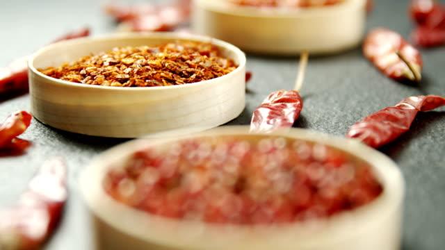 getrocknete rote chilischote und zerkleinerten paprika in schüssel 4k - chilli stock-videos und b-roll-filmmaterial