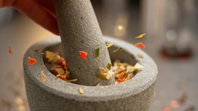 SLO MO LD Dried vegetables being crushed in a mortar with a granite pestle