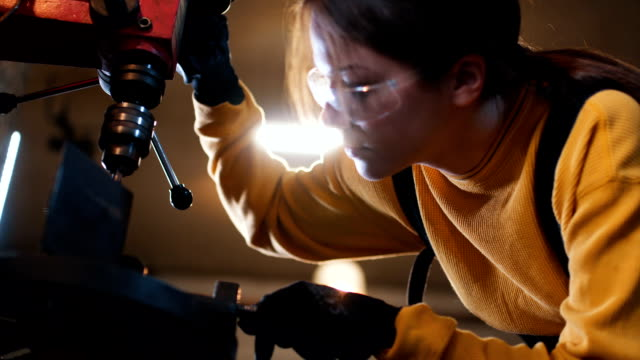 Drilling a hole in a metal part Gorgeous young girl designing a sculpture of metal, and making it. metal worker stock videos & royalty-free footage