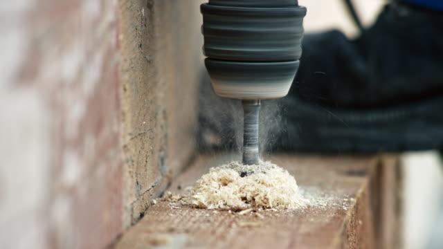 vídeos y material grabado en eventos de stock de ld perforando un agujero a través de la madera - material de construcción