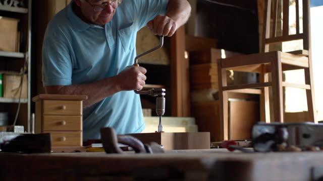 drilling holes in a wooden block - mały filmów i materiałów b-roll