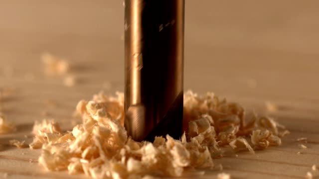 Drilling into wood close up slow motion video