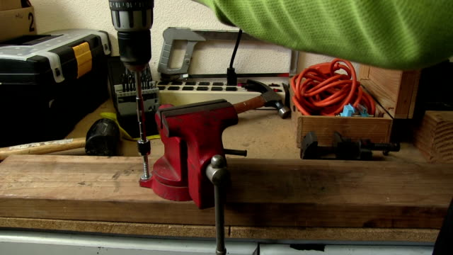 Drilling screws into red vice on workbench with sound video