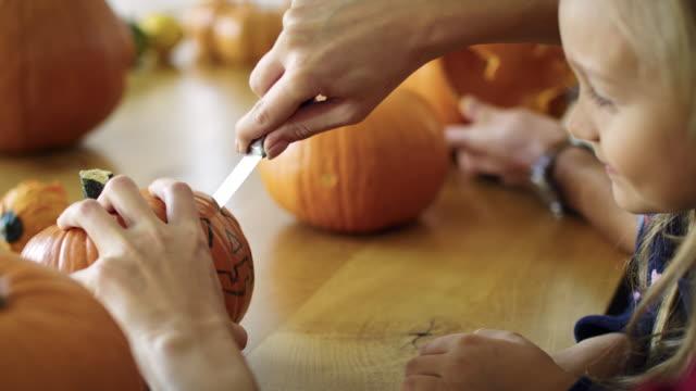 drilling small pumpkins for halloween - incisione oggetto creato dall'uomo video stock e b–roll