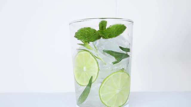 drink refreshing summer cocktail lemonade with ice,    tarragon, lime, mint, pour in glass close up