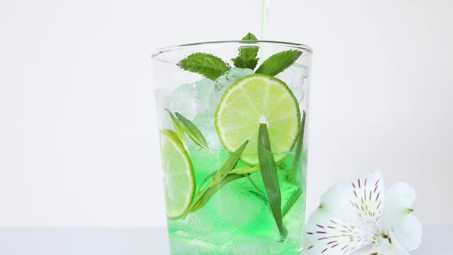 drink refreshing summer mojito cocktail lemonade with ice,    tarragon, lime, mint, pour in glass close up