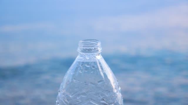 trinken sie wasser hintergrund. flasche mit wasserspritzern und meerwasser auf dem hintergrund. soziale kunst zur verhaltensänderung. mineralwasser hintergrund. mangel an trinkwasser auf der erde - altglas stock-videos und b-roll-filmmaterial