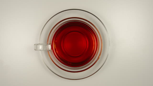 top view: drinking a black tea from a glass tea cup - stop motion - tea cup stock videos & royalty-free footage