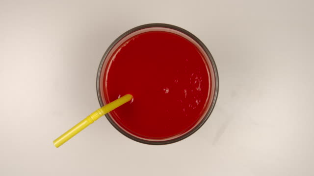 top view: drinking a fresh tomato juice by a straw - stop motion - paglia video stock e b–roll