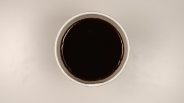 TOP VIEW: Drinking a hot dark coffee from a paper cup - Stop motion