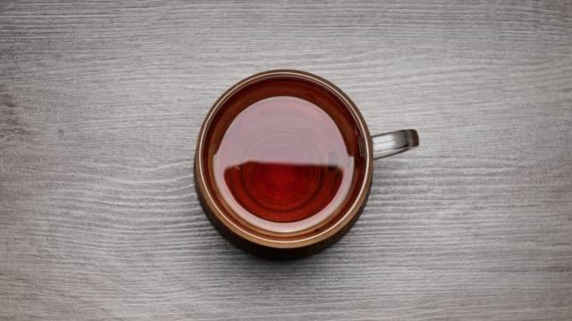 beyaz bir arka plan üzerinde bir çay fincanı siyah çay içme - hareket durdurun. time lapse fincan çay. - serinletici stok videoları ve detay görüntü çekimi