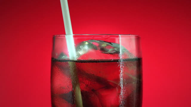 Drinking soft drink in glass with ice cube on red background. Cola or refreshment. Drinking soft drink in glass with ice cube on red background. Cola or refreshment. straw stock videos & royalty-free footage