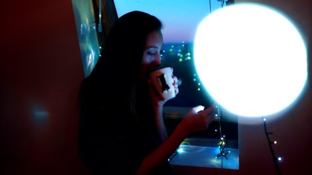 Drinking tea and using phone near window video