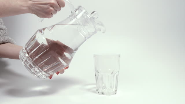 drinking water. a female hand pours water from a decanter into a glass. - decanter video stock e b–roll
