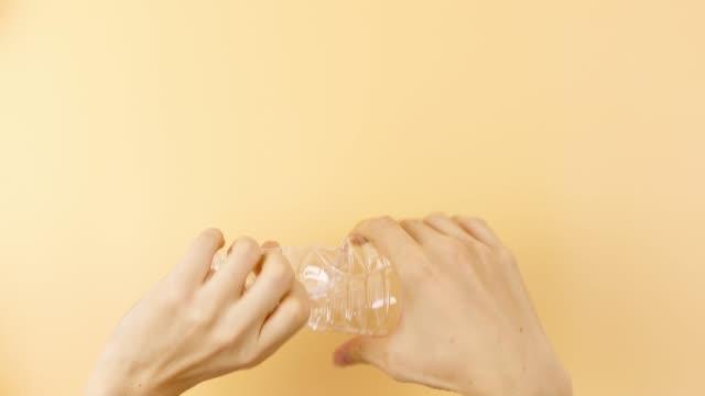 dricks vatten flaskan komprimeras med händerna. - pet bottles bildbanksvideor och videomaterial från bakom kulisserna