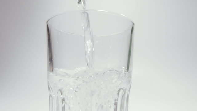 drinking water. drinking water is poured into a glass. filmed in slow motion. - decanter video stock e b–roll