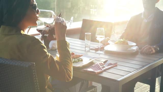Drinking white wine in outdoor restaurant video