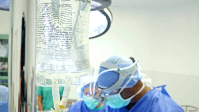 IV drip bag in operating room while surgeons are operating video