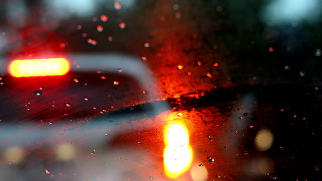 drive car in the city street with rainy day weather, rain drop on windshield with blur light of vehicle on traffic jam urban road - ingorgo stradale video stock e b–roll