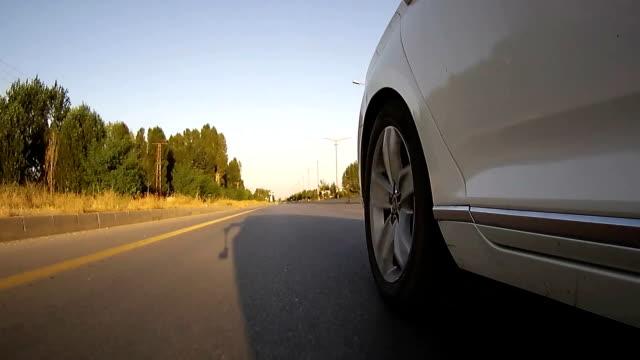 vidéos et rushes de conduire sur l'asphalte contre le coucher du soleil avec la cam de l'action. regarde un pneu de voiture sur la route. - voiture blanche