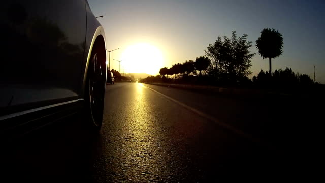 Drive on asphalt against sunset with action cam. Viewing car tire on the road.