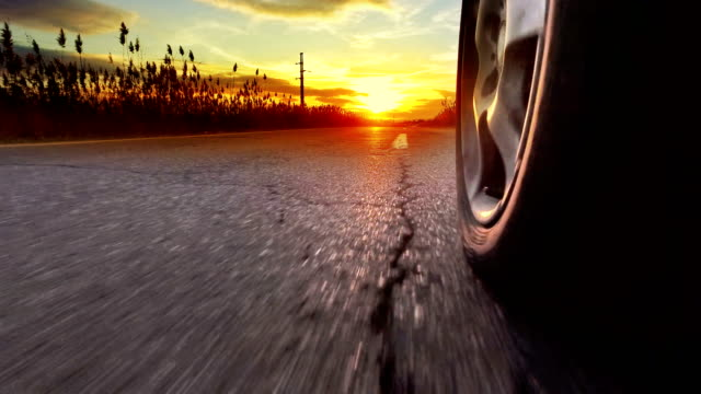 Drive on asphalt at sunset against bright setting sun with lens flare