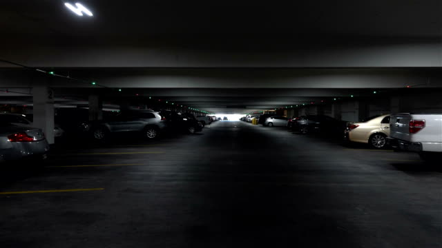 pov drive through underground parking garage in slow motion - sottosuolo video stock e b–roll