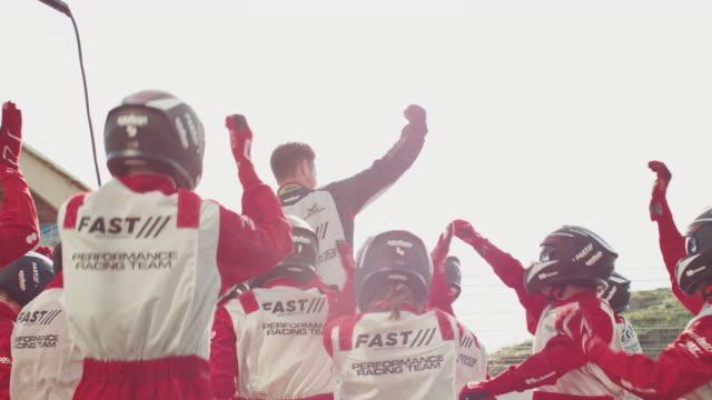 driver celebrating victory with team at pit stop - mechanik filmów i materiałów b-roll