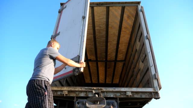 vídeos de stock, filmes e b-roll de motorista fecha as portas do reboque do caminhão estacionado no dia ensolarado de verão. caminhão estacionado na zona rural. vista de ângulo baixo lenta close-up - carregamento atividade