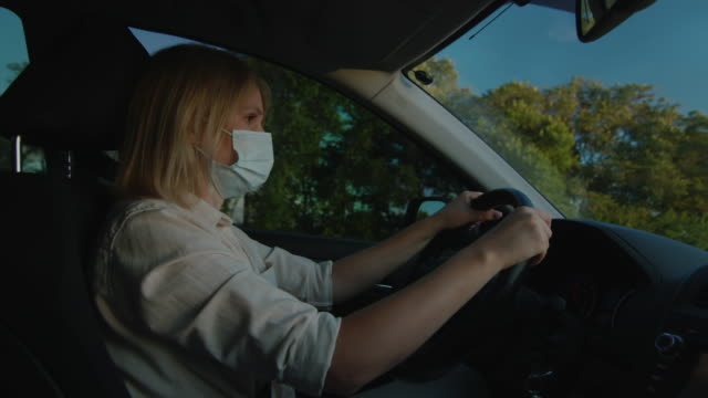 Driver in protective mask drives behind the wheel of a car video