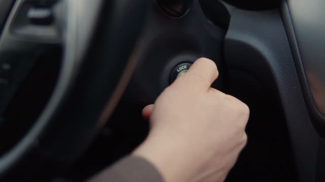 Driver is turning ignition key in automobile, close-up of hand - vídeo
