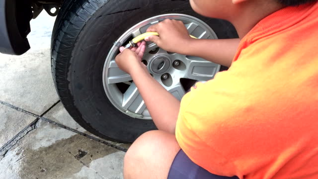 Driver putting air into a tire of his modern car