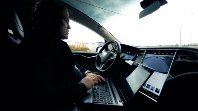 ドライバーは、ラップトップで作業しながら、オートパイロットに車に乗ります, クローズアップ. - 自動化点の映像素材/bロール