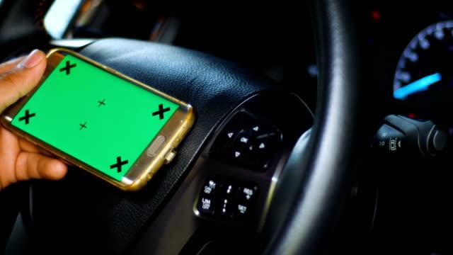 drivrutinen använder smart telefon med grön skärm i en bil, färgtransparens, dolly skott - telefonmeddelande bildbanksvideor och videomaterial från bakom kulisserna