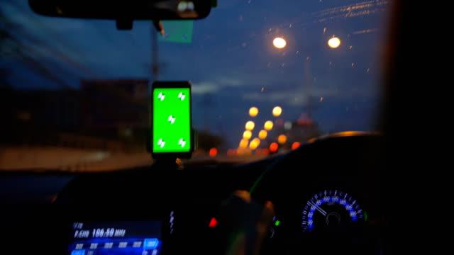 drivrutinen använder smart telefon med grön skärm i en bil - telefonmeddelande bildbanksvideor och videomaterial från bakom kulisserna