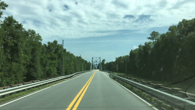 Driver view down paved highway going over suspension bridge