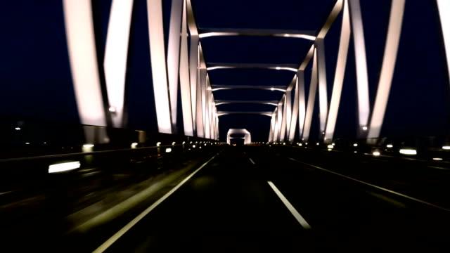 Stuurprogramma is POV via de brug boven water in schemerlicht. video