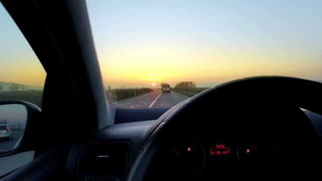 Drivers's hands on stearing wheel of a car driving toward sunset horizon video