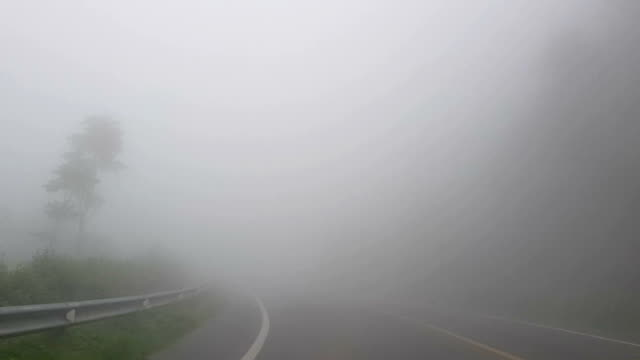 POV Drives a Car on a Foggy Road in the County at Doi inthanon, Chiang Mai, Thailand