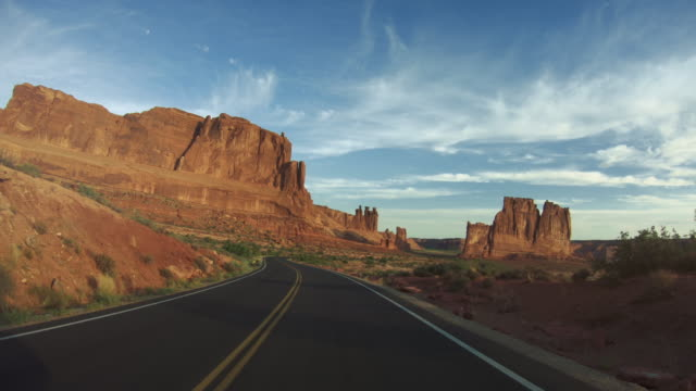 pov driving a car in arches national park - parco nazionale video stock e b–roll