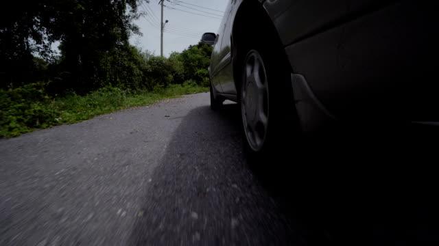 fahren ein auto auf einer landstraße. räder drehen pov. blick unter das auto - langsam stock-videos und b-roll-filmmaterial
