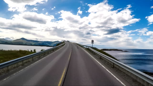 driving a car on a road in norway atlantic ocean road or the atlantic road (atlanterhavsveien) been awarded the title as (norwegian construction of the century). - oceano atlantico video stock e b–roll