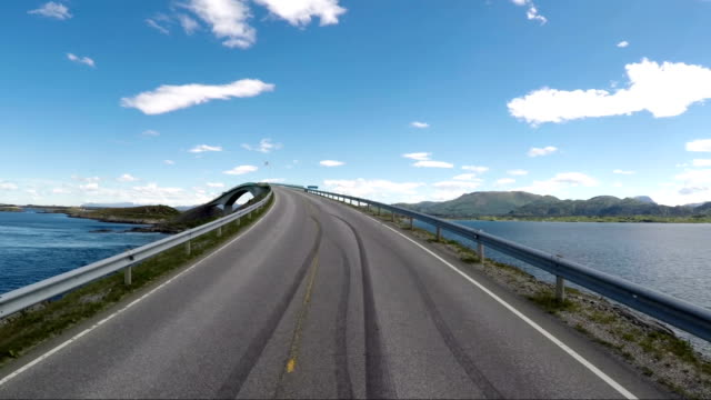 driving a car on a road in norway atlantic ocean road or the atlantic road (atlanterhavsveien) been awarded the title as (norwegian construction of the century). - autobahn video stock e b–roll