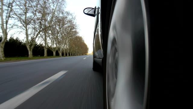 driving a car on country road. wheel spinning pov - wheel black background bildbanksvideor och videomaterial från bakom kulisserna