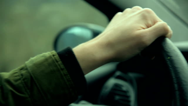 Driving a car Close-up video of human hand on the steering wheel in moving car. wheel stock videos & royalty-free footage