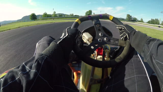 POV: Driving a go-kart in a black suit through sharp bends of a bumpy racetrack.