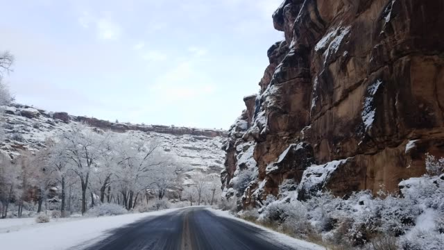 Driving Along a Road through a Snowy, Hilly Desert Landscape in Winter Driving Along a Road through a Snowy, Hilly Desert Landscape in Winter country road stock videos & royalty-free footage