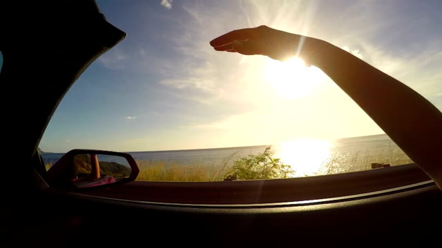 SLOW MOTION: Driving along the beach at sunrise hand waving in the summer wind SLOW MOTION CLOSE UP: Driving in red convertible, arm outside of car playing with wind against the sunset sky. Unrecognizable female waving with her hand in wind on summer vacation in Hawaii island rear view mirror stock videos & royalty-free footage