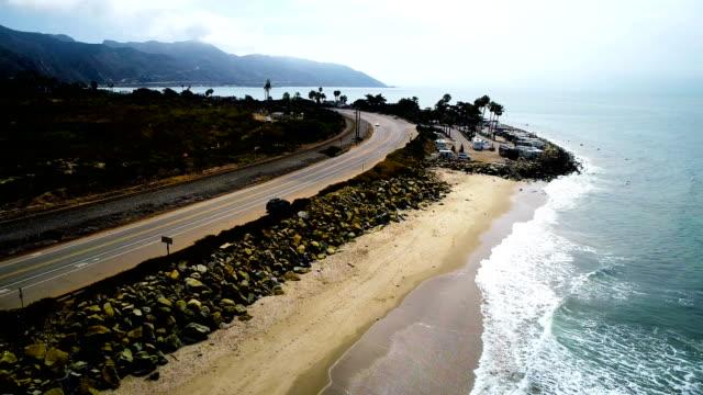 vídeos de stock e filmes b-roll de rv driving by on the pacific coast highway aerial drone view - estrada 001