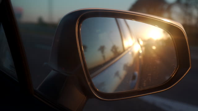 Driving car at sunset sun rays cars reflected in side rearview mirror closeup